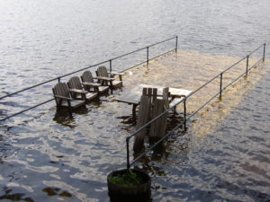 High water on Berry Bay swamps a dock in April 2007. In addition to major damaging floods, such as those in 1953, 1998 and 2005, nuisance floods that linger for days are common on Ossipee Lake, creating hazards by sending personal property and debris out into the lake. Alliance Photo